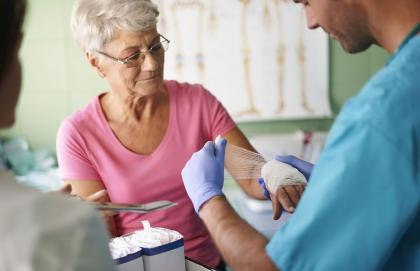 Young provider wraps elderly female patient's wrist with gauze.