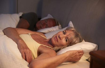 Woman who is awake, lying next to sleeping man