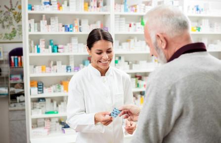 A pharmacist handing medication to a customer
