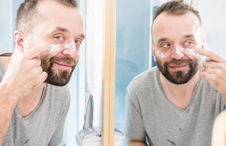 Man moisturizing face