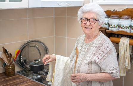 Senior citizen cooking at stove