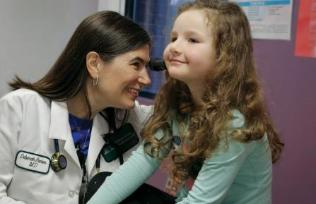 Pediatric provider with patient checking patient's ear